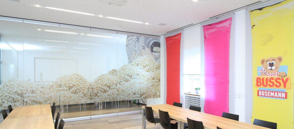 Konferenzraum mit bedrucktem Raumtrenner und Gardinen al Wassereis